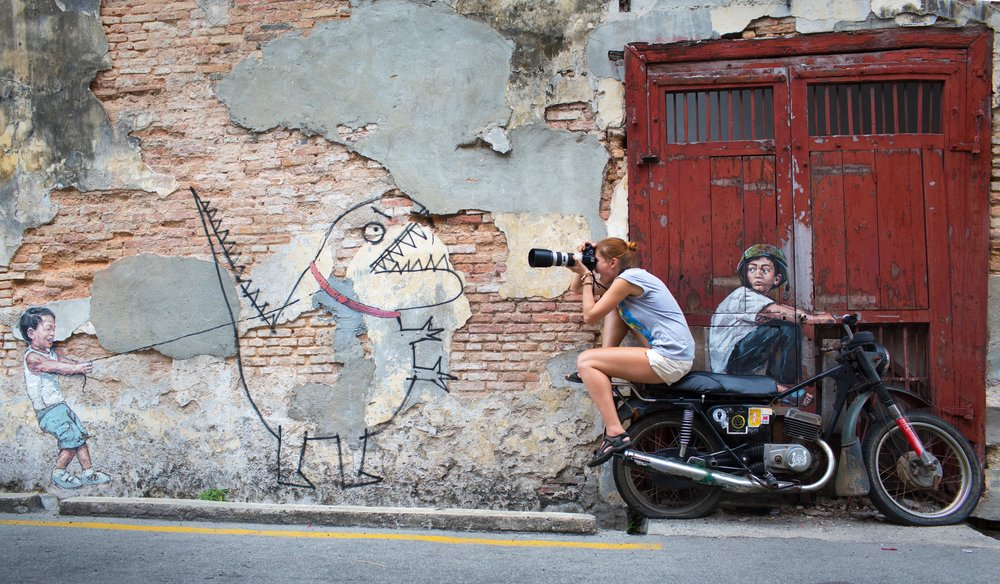 A girl riding the motorcycle street art while photographing the other kid street art
