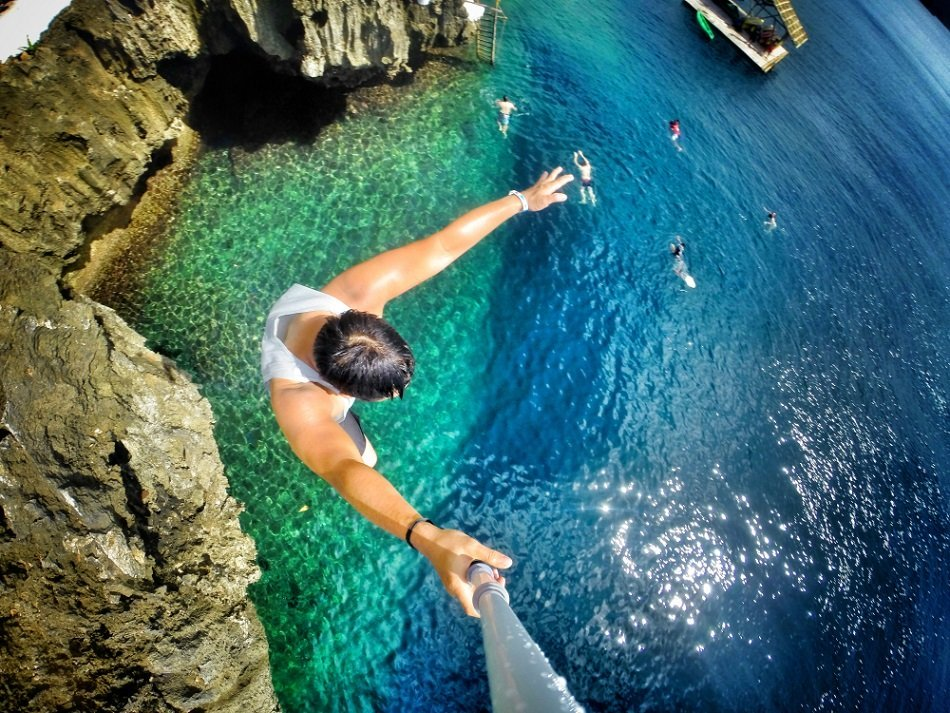 a man diving on a cliff