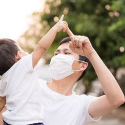 asian baby boy playing with dad while wearing masks